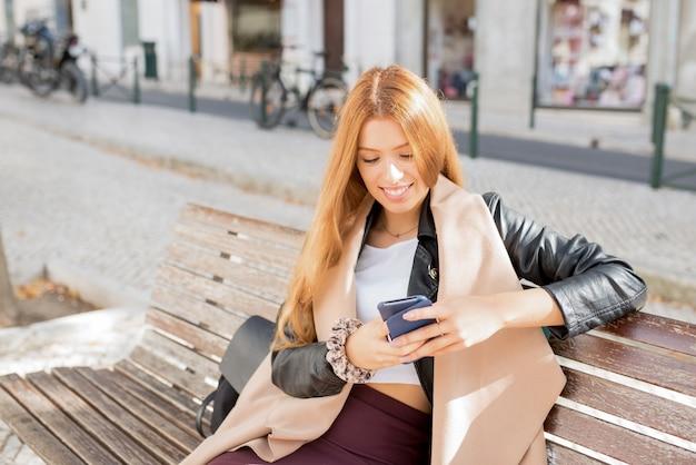 Positive frau, die sms simst und auf bank sitzt