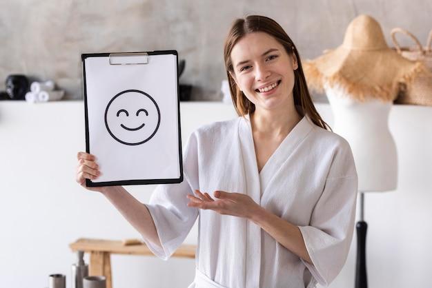 Positive frau, die zwischenablage mit smiley hält