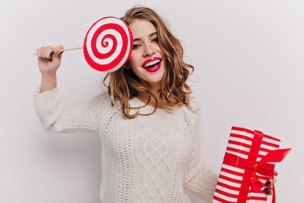 Positive frau im niedlichen gestrickten outfit, das mit süßigkeiten aufwirft und im urlaub präsentiert. innenporträt des attraktiven europäischen weiblichen modells, das rote geschenkbox und süßigkeiten hält.