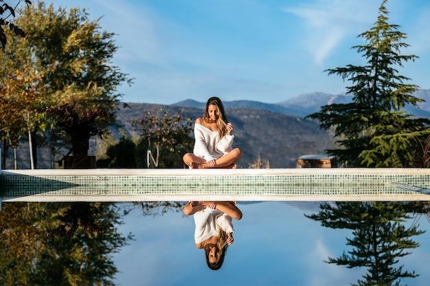 Positive frau im weichen pullover lächelnd und schließende augen beim entspannen an der grenze im hof auf unscharfem hintergrund der berge
