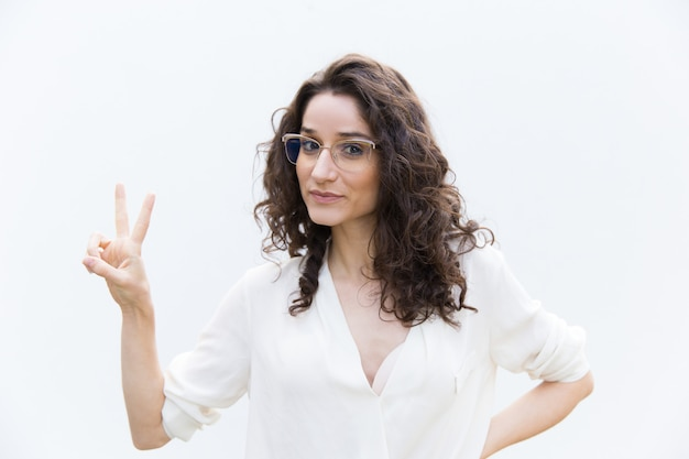 Positive frau in den gläsern, die siegesgeste zeigen