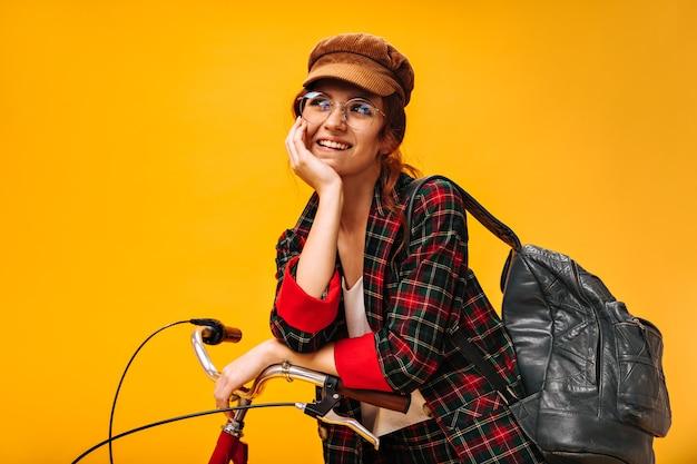 Positive frau in samtmütze und brille posiert verträumt mit fahrrad