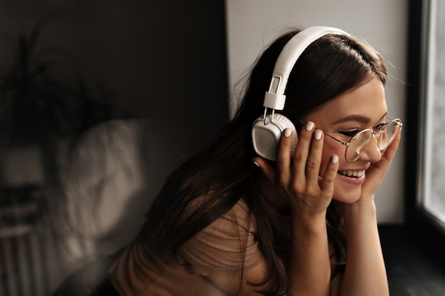 Positive frau in weißen massiven kopfhörern setzt brille auf und lächelt, stützt sich auf schwarzes fensterbrett.