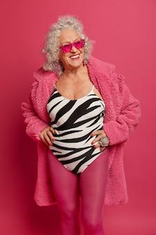 Positive frau mit grauem haar, lächelt breit, hält die hände an der taille, hält sich fit und gesund, trägt eine trendige sonnenbrille, einen badeanzug, rosa strumpfhosen und eine robe und träumt von urlaub während der selbstisolation