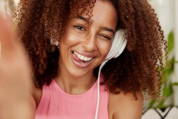 Positive frau mit krauser buschiger frisur zeigt zunge, macht selfie mit unerkennbarem gerät verbunden, hört lieblingslieder in der wiedergabeliste mit kopfhörern, genießt freizeit alleine. ethnizität, lebensstil