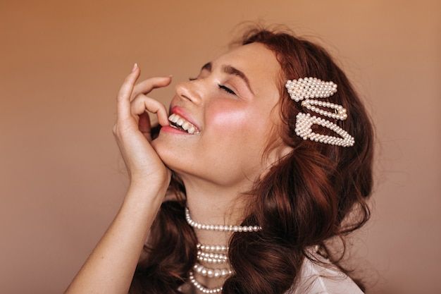 Positive frau mit lockigem haar lacht und beißt sich auf den finger. porträt der frau mit weißen haarnadeln und perlenkette.