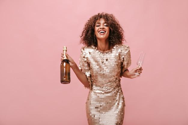 Positive frau mit lockiger, flauschiger frisur in glänzender moderner kleidung, die lacht und flasche mit wein und glas an rosa wand hält..