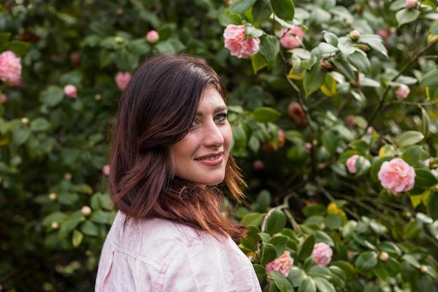 Positive frau nahe den rosa blumen, die auf grünen zweigen des busches wachsen
