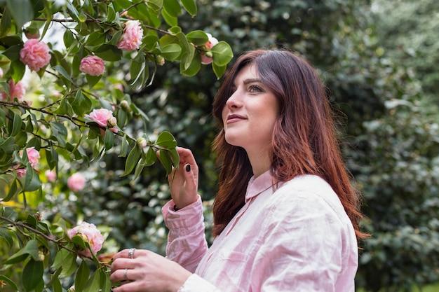 Positive frau nahe den rosa blumen, die auf grünen zweigen wachsen