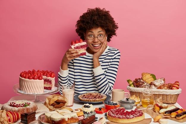 Positive frau naschkatzen schmeckt köstlichen erdbeerkuchen, bricht diät und isst viel kalorien essen, sitzt an einem großen tisch mit süßwaren
