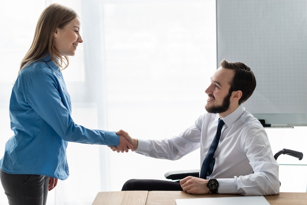 Positive frau und mann händeschütteln zusammen