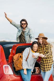 Positive frauen, die selfie auf smartphone nahe dem autokofferraum nehmen und mann, der sich heraus vom auto lehnt
