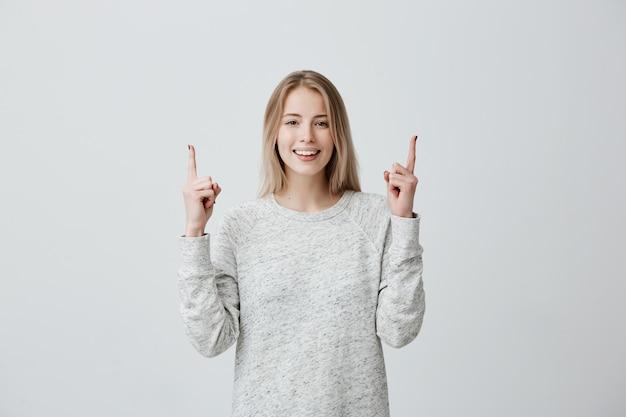 Positive freudige blonde frau, die mit zeigefingern auf kopienraum zeigt.