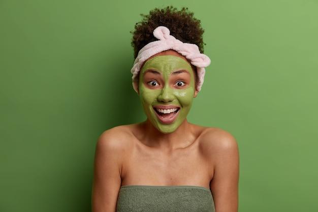 Positive freudige frau trägt nährstoffgrüne maske auf gesicht auf, hat tägliche hygieneroutine, macht schönheitsanwendungen am morgen, lacht glücklich, hat gesunde strahlende haut, eingewickelt in badetuch, steht drinnen