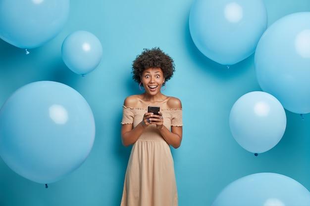 Positive fröhliche afroamerikanerin hält handy in händen und freut sich, mit freunden in sozialen netzwerken zu chatten, trägt cocktailkleid, posiert gegen blaue wand in dekorierter fotozone