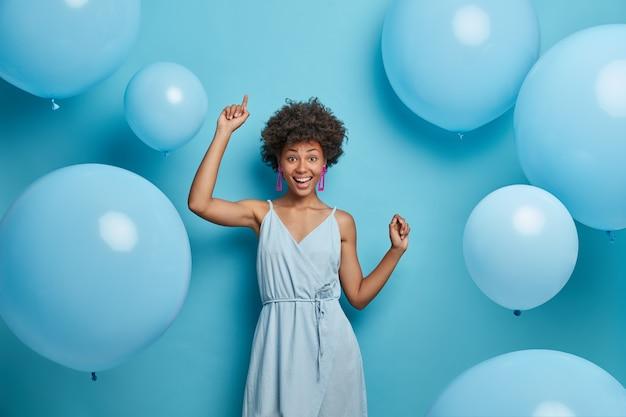 Positive fröhliche festliche frau mit hollywood-lächeln, lacht vor freude, bewegt sich sorglos und tanzt zur musik, hat spaß, macht fröhliche urlaubsfotos, feiert jubiläum, umgeben von luftballons.