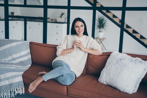 Positive fröhliche frau sitzen auf braunem leder diwan halten tasse mit latte cappuccino starren fenster fühlen sich inspiriert fantasie verträumt im haus drinnen