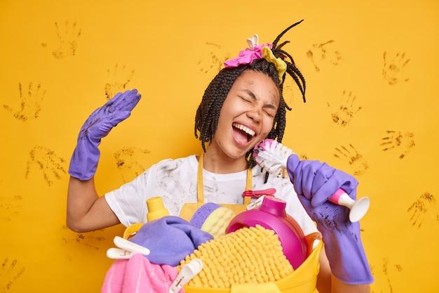 Positive fröhliche hausfrau singt lied mit, hält bürste, als ob mikrofon schmutzige kleidung trägt, steht in der nähe des wäschekorbs trägt gummihandschuhe, albert um die gelbe wand herum