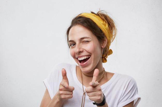Positive fröhliche junge frau, die gelben schal auf kopf und weißes lässiges t-shirt trägt, das ihre augen blinzelt und mit zeigefingern lächelnd zeigt. glückliche attraktive frau, die auf sie zeigt