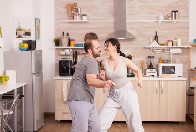 Positive fröhliche verrückte paare tanzen beim frühstück in der küche im pyjama. sorglose frau und ehemann lachen spaß haben lustig das leben genießen authentische verheiratete menschen positive glückliche beziehung