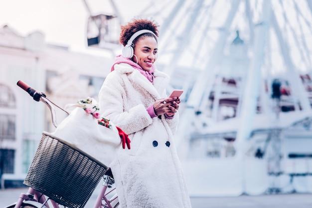 Positive gedanken. hübsche weibliche person, die lächeln auf ihrem gesicht hält, während sie sich auf fahrrad stützt