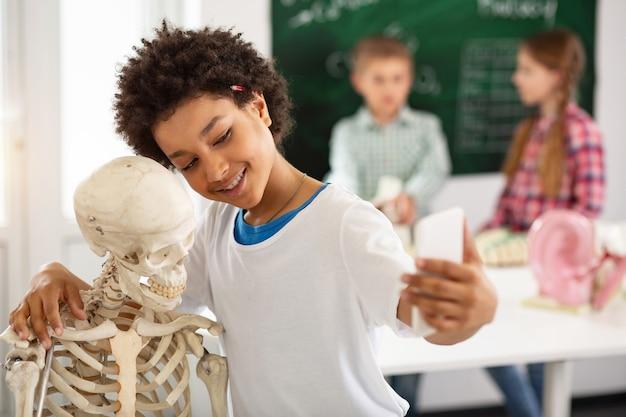 Positive gefühle. erfreuter netter junge, der lächelt, während er ein selfie mit einem skelett macht