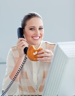 Positive geschäftsfrau am telefon eine donna essend
