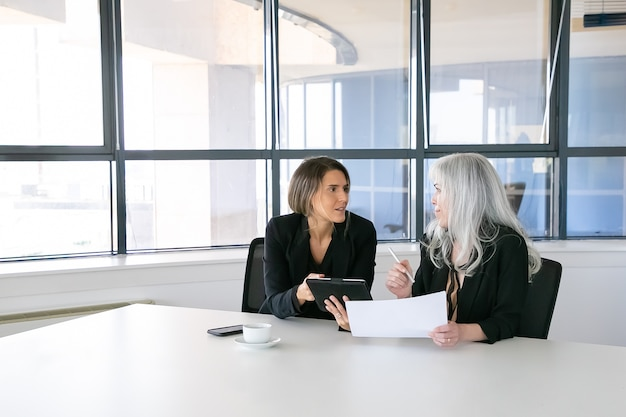 Positive geschäftsfrauen diskutieren und analysieren berichte. zwei weibliche angestellte sitzen zusammen, halten dokumente, benutzen tablett und sprechen. teamwork-konzept