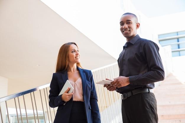 Positive geschäftsleute, die tabletten auf treppe sprechen und halten