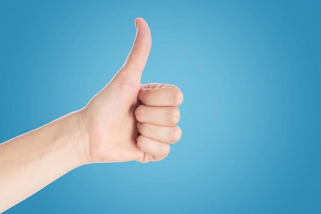 Positive geste auf blauem grund. handshowdaumen up zeichen, abschluss oben