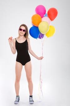 Positive glücklich lächelnde süße hübsche hübsche mädchen im schwarzen badeanzug mit bunten luftballons und kleinen makronen Premium Fotos