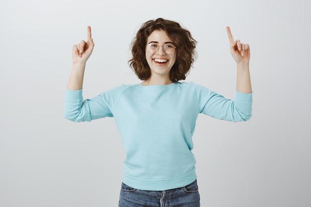 Positive glückliche frau, die finger nach oben zeigt und lächelt