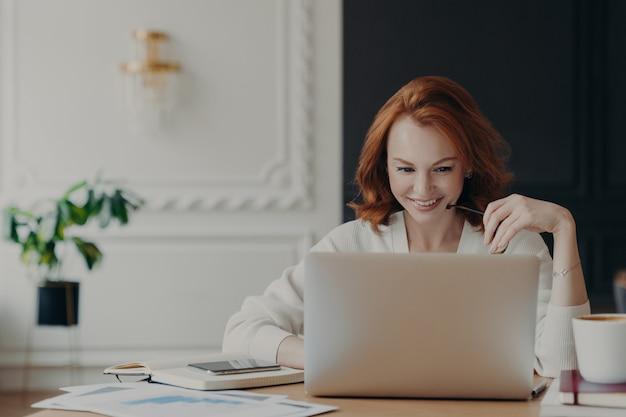 Positive glückliche freiberuflerin hat viel zu tun, arbeitet fern von zu hause, sitzt vor einem laptop gegen ein modernes interieur, arbeitet an kreativen aufgaben und sieht sich ein webinar zur verbesserung der fähigkeiten an