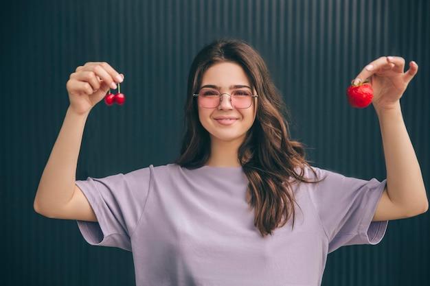 Positive glückliche fröhliche frau, die kirschen und erdbeere in den händen hält und zeigt