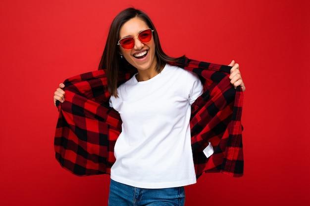 Positive glückliche lächelnde junge brünette frau im lässigen weißen t-shirt für modell, stilvolles rotes karohemd und trendige rote sonnenbrille lokalisiert auf rotem hintergrund mit kopienraum. Premium Fotos