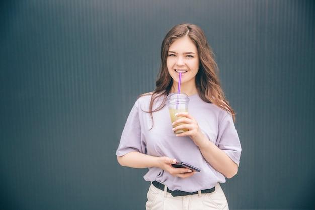 Positive, glückliche und schöne frau, die kalte erfrischende limonade trinkt und aufwirft