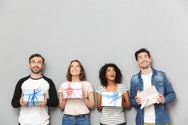 Positive gruppe von freunden, die geschenkboxen halten.