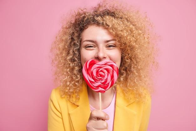 Positive gut aussehende frau mit lockigem, buschigem haar hält herzförmigen lutscher über dem mund hat süße zähne wie süßigkeiten in elegantem outfit, isoliert über rosafarbener wand. junk-food-konzept
