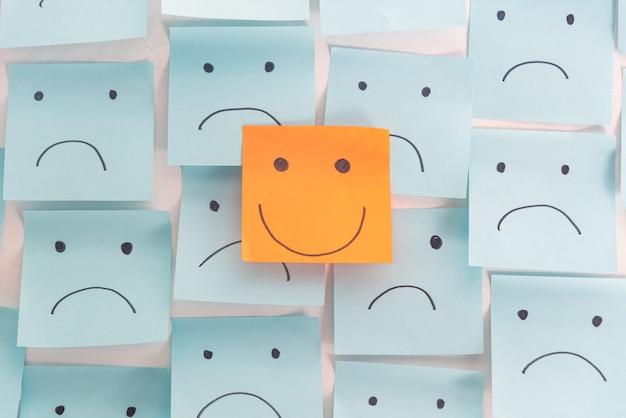 Positive haltung und glückliches konzept. hand gezeichnet ein lächelngesicht und traurige gefühl auf klebrigem nicht