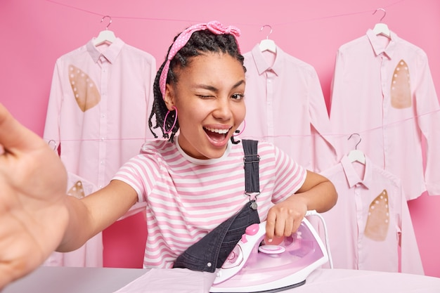 Positive hausfrau hat spaß beim bügeln von kleidung zu hause hält die arme ausgestreckt, um ein selfie-lächeln zu machen, zwinkert das auge, das an häuslichen aktivitäten beteiligt ist, verwendet elektrisches bügeleisen hat einen glücklichen ausdruck