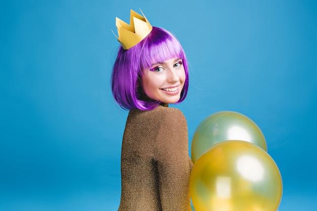 Positive helle gefühle der freudigen jungen frau mit geschnittenem lila haar feiern party mit luftballons. goldene krone, fröhliche stimmung, feiertagsfeier, geburtstag.