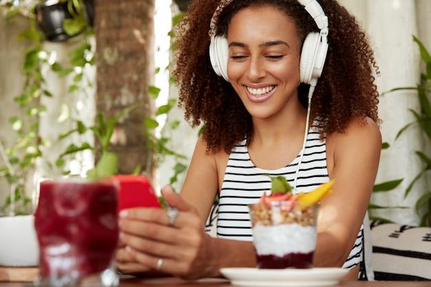 Positive hipster afroamerikanerin sucht neue musik songs, glücklich, nachricht auf dem handy zu erhalten. musikliebhaberin hört komposition aus der wiedergabeliste, gibt text-sms in sozialen netzwerken ein
