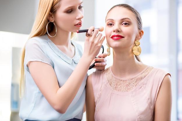 Positive hübsche frau, die lächelt, während sie sich über ihr make-up freut