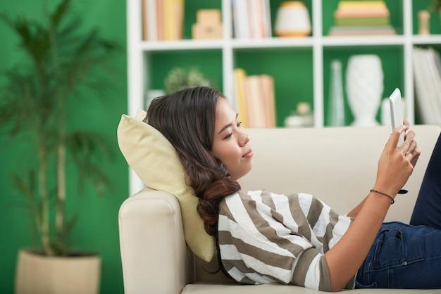 Positive hübsche junge frau, die sich zu hause auf dem sofa entspannt und lehrvideos oder -filme auf einem tablet-computer ansieht