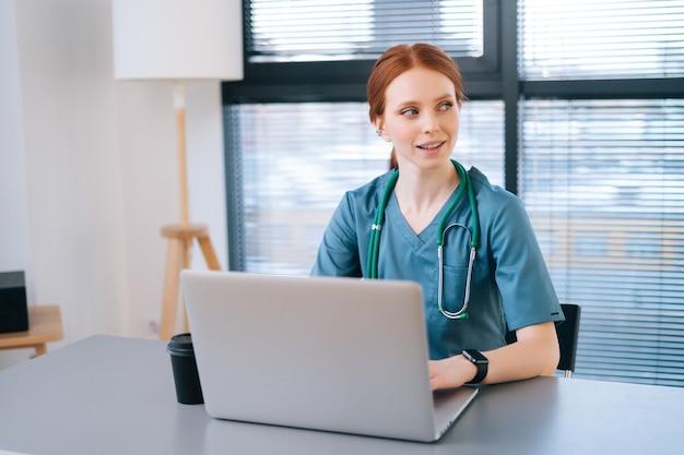 Positive junge ärztin in blauer medizinischer uniform, die auf der laptop-tastatur am schreibtisch sitzt