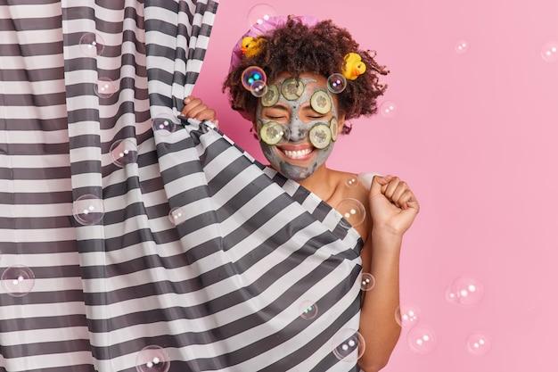 Positive junge afroamerikanische frau trägt schönheitsmaske mit gurkenscheiben auf. clenches faust hat spaß, während duschhäute hinter vorhangposen gegen rosa wand nehmen