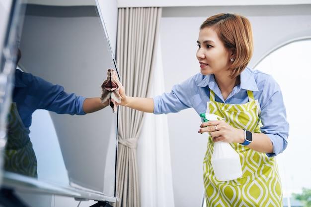 Positive junge asiatische frau, die staub vom fernsehbildschirm mit weichem tuch abwischt