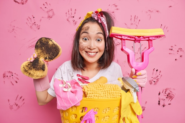 Positive junge asiatische frau hält schmutzigen schwamm und mopp, der damit beschäftigt ist, die tägliche routine zu hause zu waschen, wäsche zu entfernen, schmutz überall einzeln über rosa studiowand zu entfernen