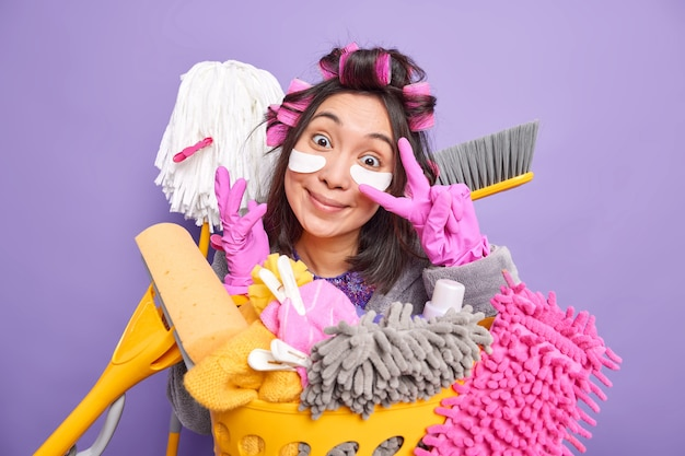 Positive junge asiatische frau macht friedensgeste über dem auge lächelt glücklich macht die frisur beschäftigt mit der reinigung verwendet besen und mopp wäscht wäsche einzeln über lila wand