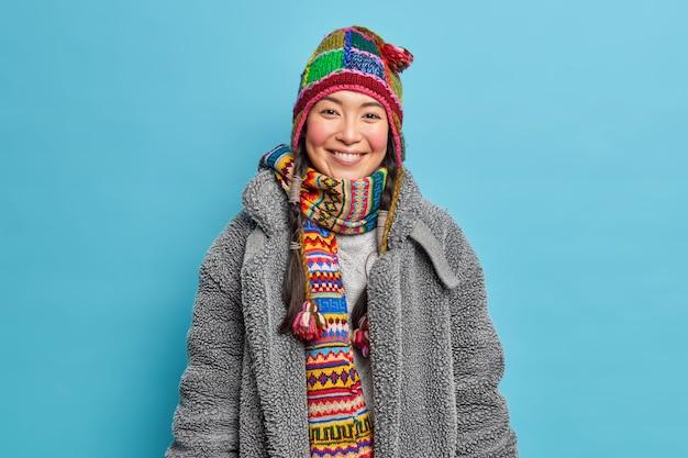 Positive junge asiatische frau mit rouge wangen lächelt glücklich trägt strickmütze und schal um den hals gekleidet in warmen mantel, um freizeit im freien während des wintertages zu verbringen, mag kaltes wetter